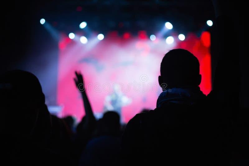 Силуэты толпы концерта перед загоренным этапом в ночном клубе стоковое изображение rf