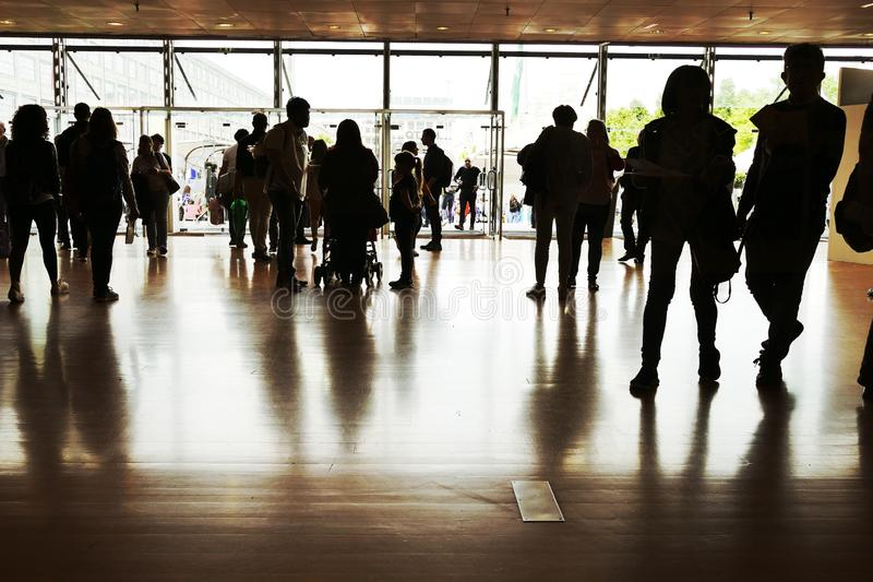 Силуэты толпы на парадном входе выставочного центра стоковые изображения