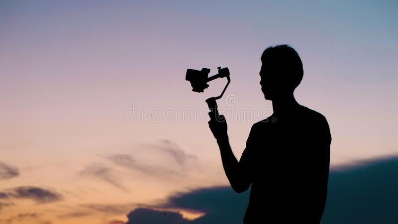 Силуэты туристского человека со стабилизатором и концом видеокамеры вверх стоковое фото rf