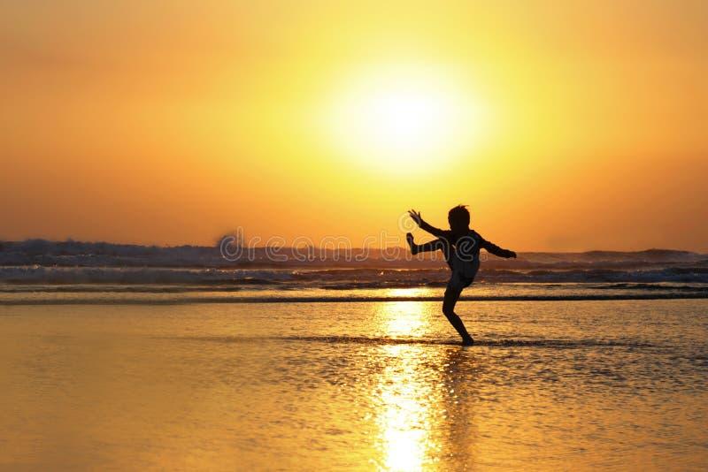 Силуэт анонимного неизвестного молодого парня имея потеху играя на морской воде на пляже пиная на влажном песке с изумлять красив стоковое фото rf