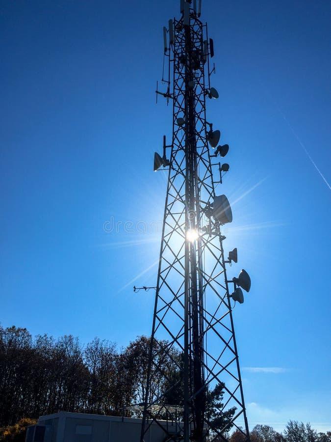 Силуэт антенн высоких клетчатых базовой станции радиосвязи на солнечный день стоковые изображения rf