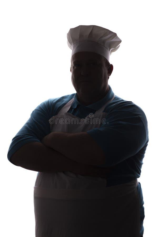 Силуэт бак-bellied уживчивого смешного шеф-повара в шляпе, мужской плита сложил его оружия над его комодом на белом изолированном стоковое фото rf