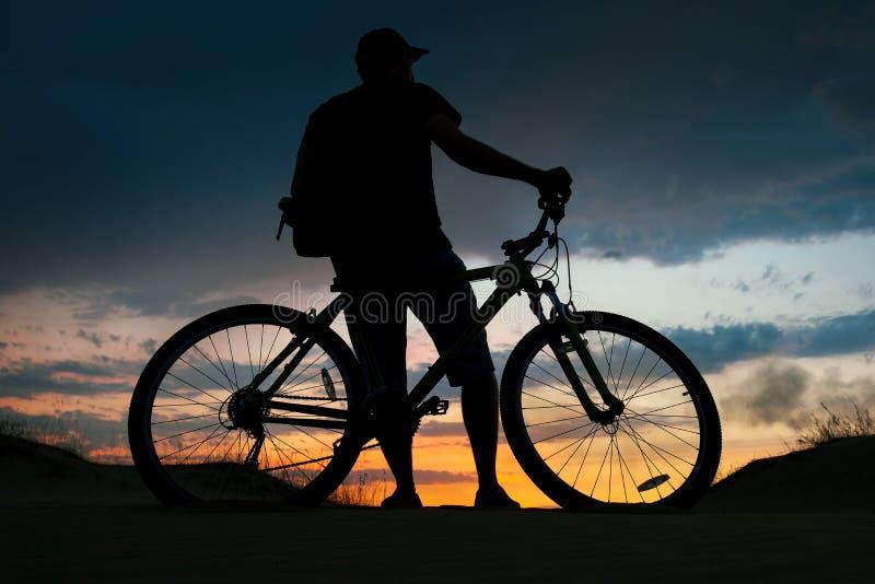 Силуэт велосипедиста на предпосылке захода солнца стоковое изображение rf
