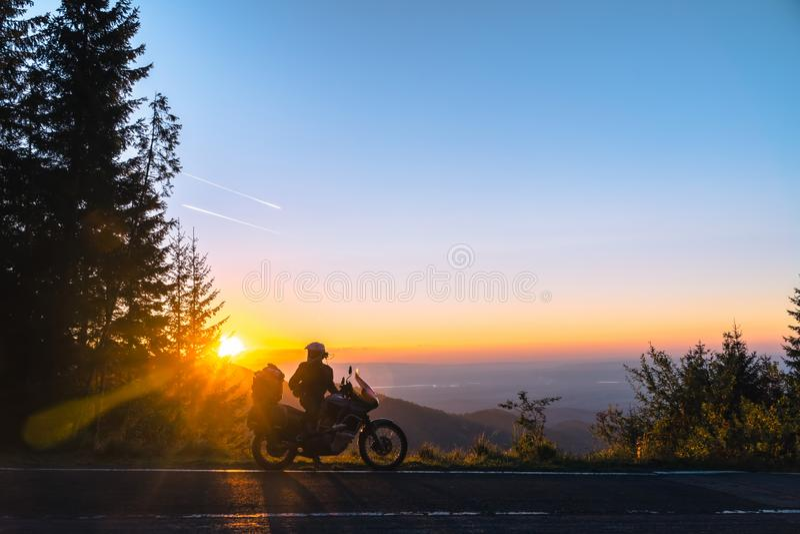 Силуэт велосипедиста человека и мотоцикла приключения на дороге с предпосылкой света захода солнца Верхняя часть гор, мотоцикл ту стоковые изображения rf