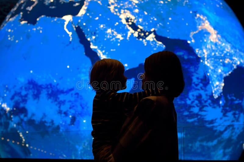 Силуэт взрослого и ребенка на предпосылке земли глобуса стоковые изображения