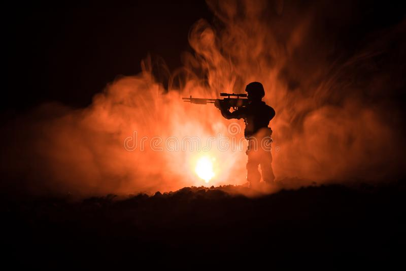 Силуэт воинского снайпера с оружием снайпера на темной тонизированной туманной предпосылке съемка, держа оружие, красочное небо,  стоковые изображения rf