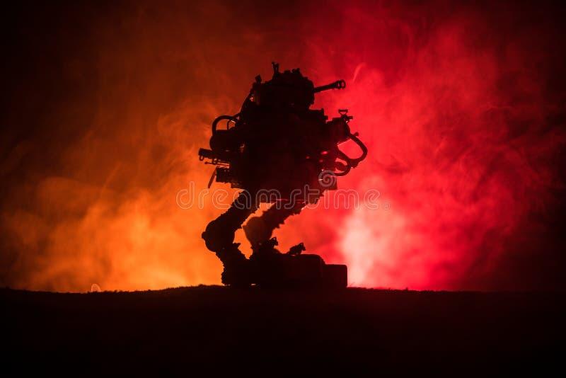 Силуэт гигантского робота Футуристический танк в действии с туманной предпосылкой неба огня стоковая фотография rf