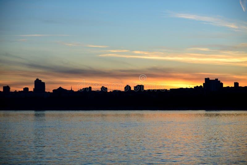 Силуэт города рекой на заходе солнца стоковое фото rf
