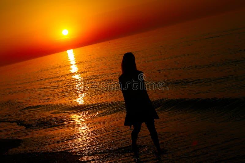 Силуэт дамы бежать морем стоковые фотографии rf