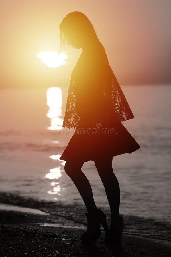 Силуэт дамы идя морем стоковая фотография