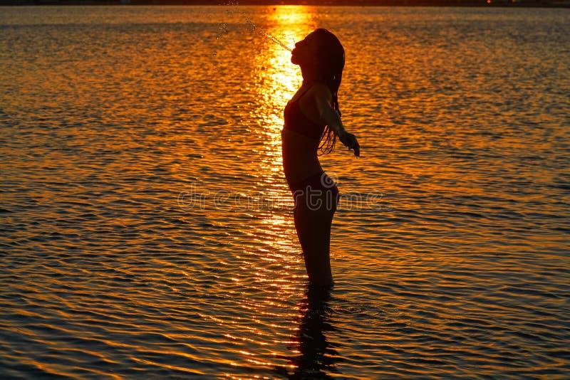 Силуэт девушки на оружиях захода солнца пляжа открытых стоковое фото rf