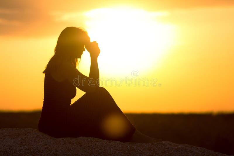 Силуэт девушки сидя на песке и моля к богу на заходе солнца, диаграмме молодой женщины на пляже, вероисповеданию концепции стоковое фото