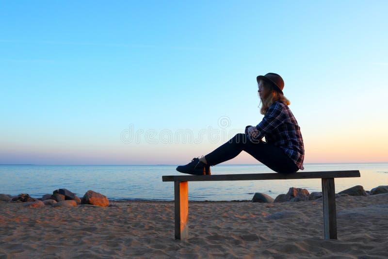 Силуэт девушки сидя на стенде над взглядом берега моря стоковое изображение rf
