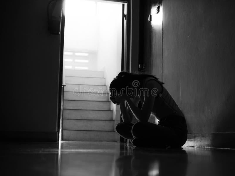 Силуэт девушки сидя самостоятельно в темноте, насилии в семье, проблемах семьи, стрессе, насилии, концепции депрессии и стоковые изображения rf