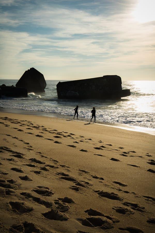 Силуэт детей бежать на песчаном пляже в сценарном красивом seascape с волнами в заднем освещении стоковое фото rf