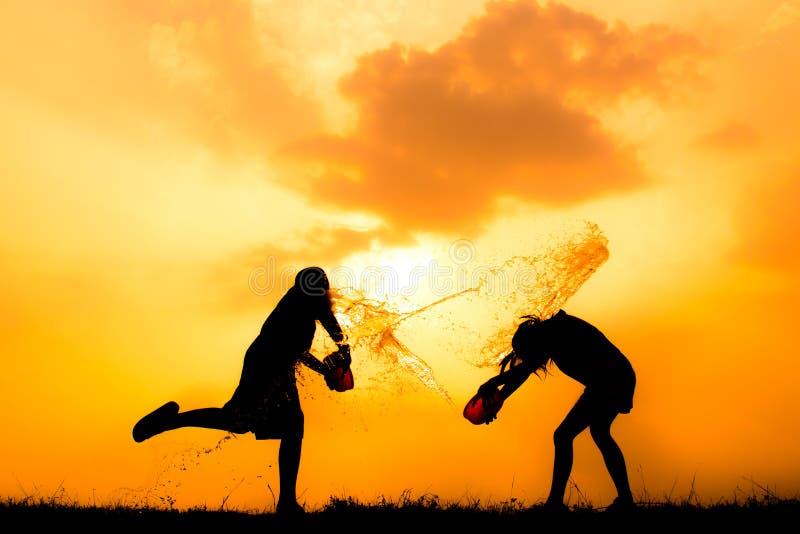 Силуэт детей играя воду во время захода солнца неба стоковое изображение rf