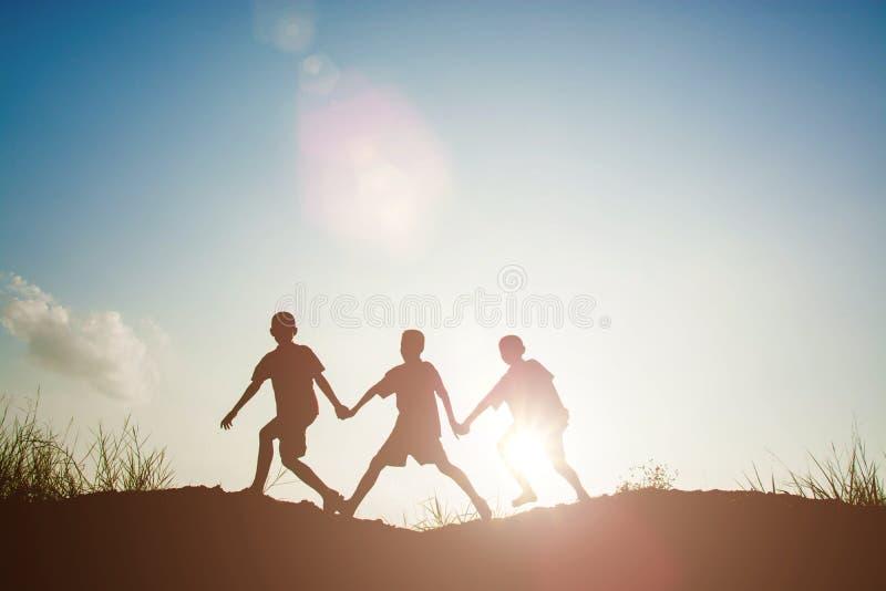 Силуэт детей играя во времени захода солнца парка стоковое изображение rf
