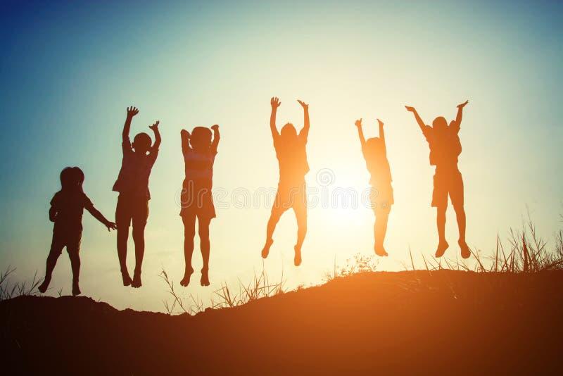Силуэт детей скачет время gladness счастливое стоковое изображение rf