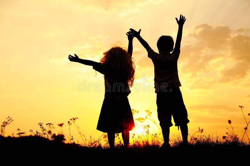 силуэт детей счастливый играя стоковые изображения rf