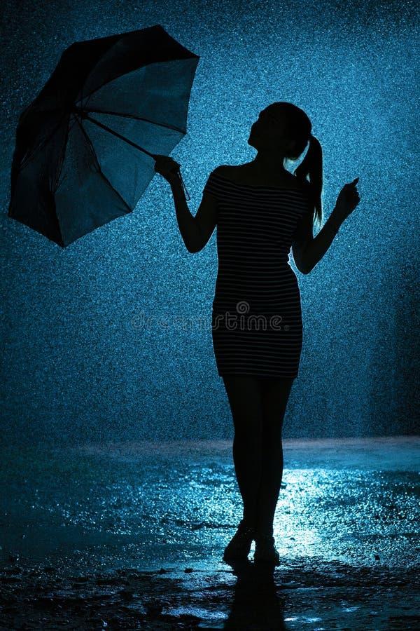 Силуэт диаграммы маленькой девочки с зонтиком в дожде, молодая женщина счастлив к падениям воды, погоды концепции стоковое изображение rf