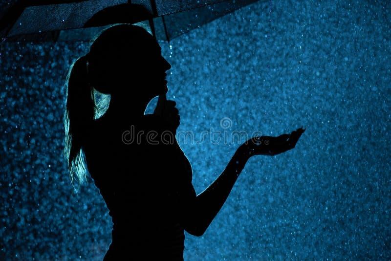 Силуэт диаграммы маленькой девочки с зонтиком в дожде, молодой женщине счастливой к падениям воды стоковая фотография