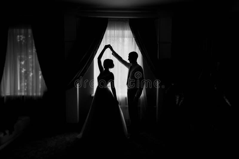 Силуэт жениха и невеста окном стоковые изображения