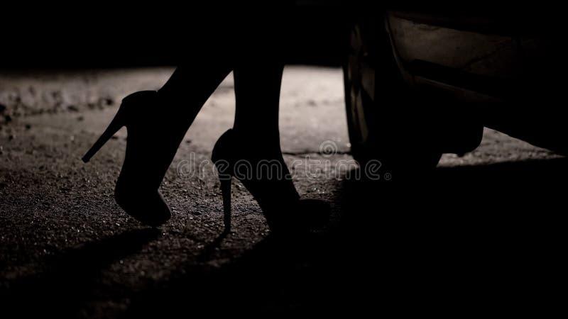 Силуэт женских ног в высоких пятках приходя к автомобилю, проституции, туризму секса стоковые фотографии rf
