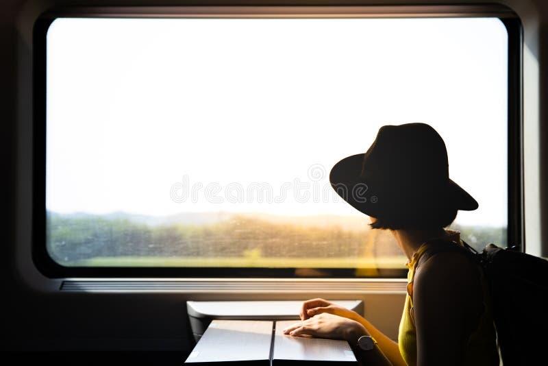 Силуэт женщины красивого битника азиатской путешествуя на поезде стоковые фото