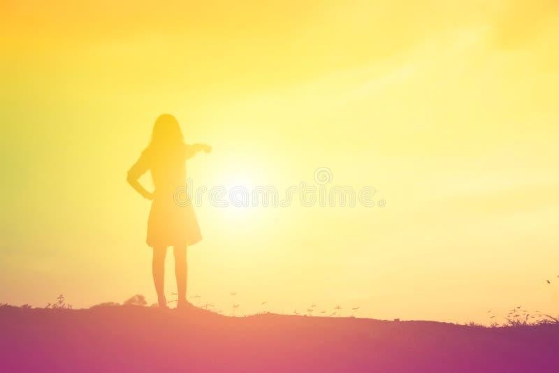 Силуэт женщины моля над красивой предпосылкой неба стоковое фото rf