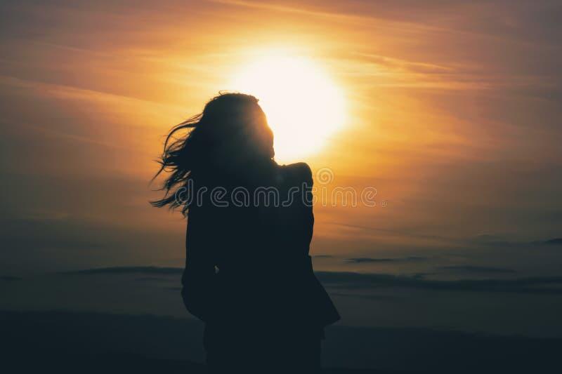 Силуэт женщины на заходе солнца стоковая фотография rf