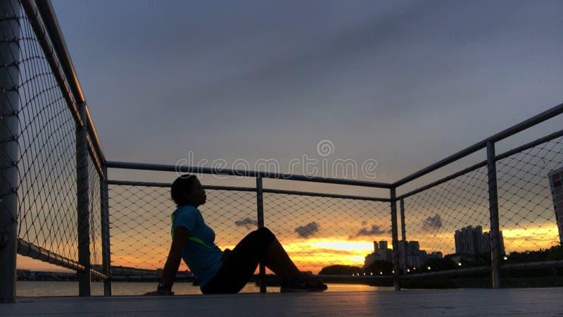 Силуэт женщины против захода солнца на пристани стоковое фото