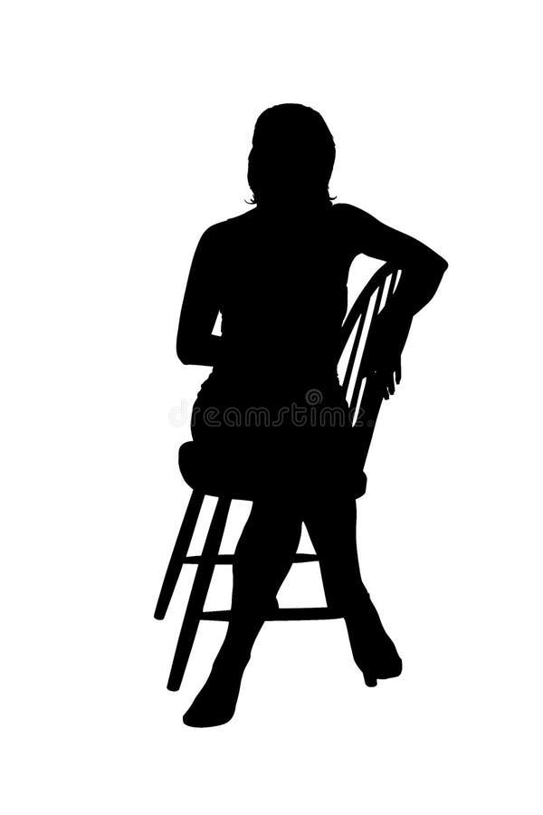 Силуэт женщины сидя на стуле стоковая фотография rf