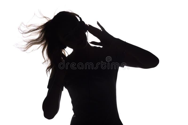 Силуэт женщины слушая к музыке в наушниках стоковые фото