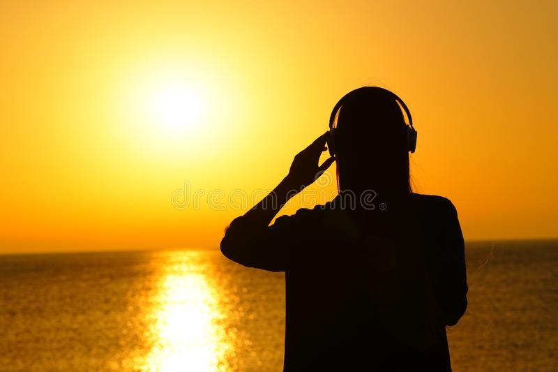 Силуэт женщины слушая музыку на заходе солнца стоковые изображения