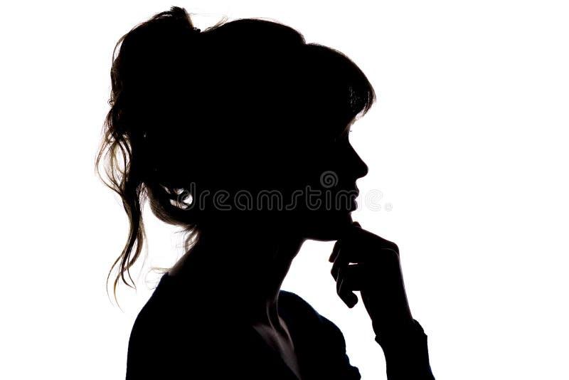 Силуэт заботливой красивой девушки с рукой около ее подбородка думая о разрешать проблему стоковые изображения rf