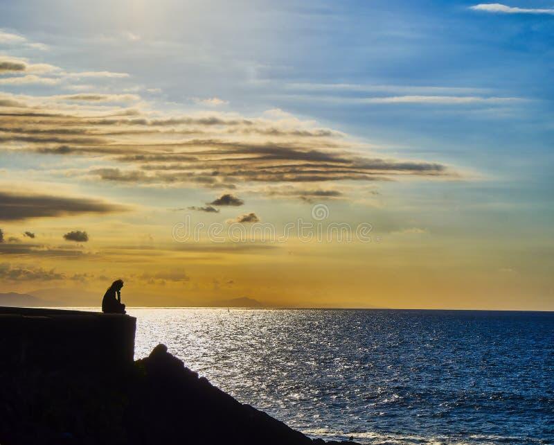 Силуэт задумчивой женщины сидя на стене стоковая фотография rf