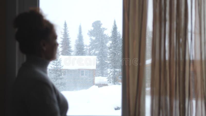 Силуэт запачканной зрелой женщины в постаретый наблюдать в окне на красивых снежных горах стоковые изображения