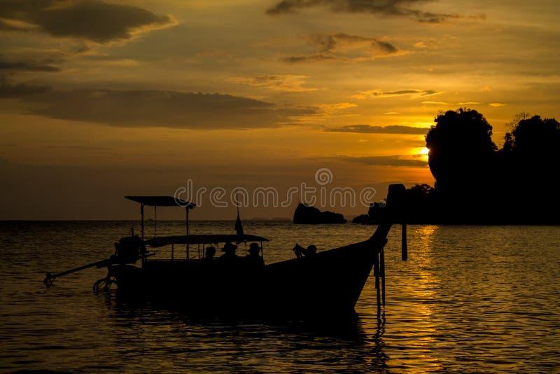 Силуэт захода солнца залива шлюпки длинного хвоста на море в Таиланде стоковое изображение rf