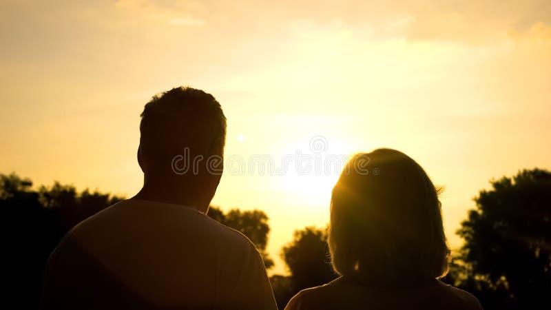 Силуэт захода солнца старших пар наблюдая совместно, безопасная старость, благополучие стоковые фотографии rf