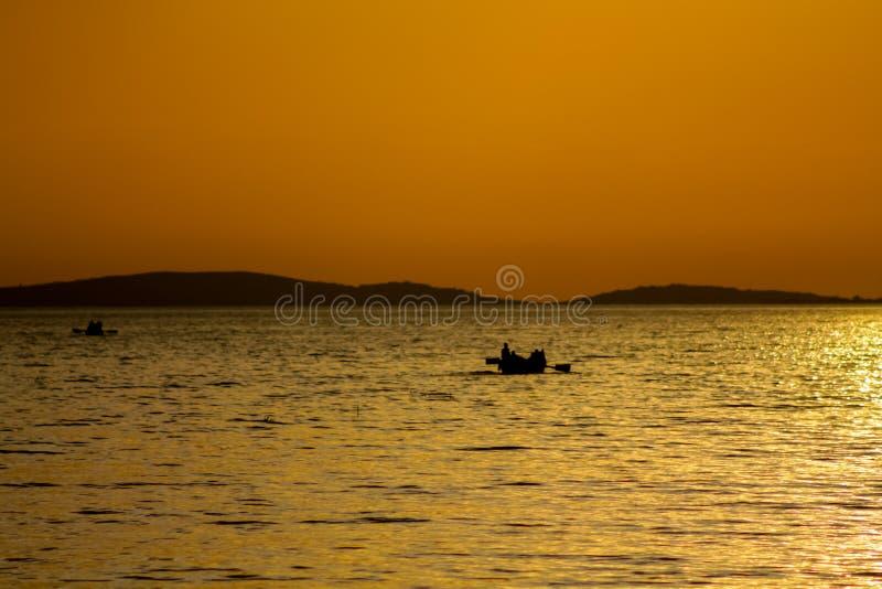Силуэт захода солнца шлюпки на озере стоковые изображения