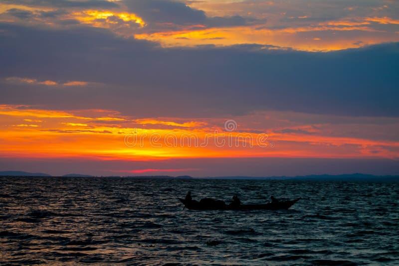 Силуэт захода солнца шлюпки на озере стоковое изображение rf