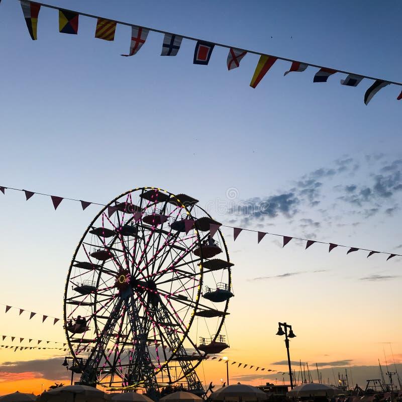 Силуэт колеса Ferris против оранжевого голубого неба захода солнца в ночи лета стоковое изображение