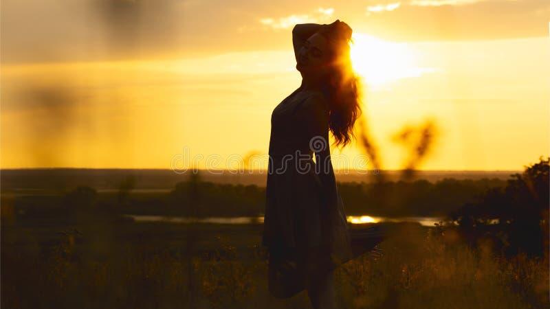 Силуэт красивой девушки в платье на заходе солнца в поле, диаграмме молодой женщины наслаждаясь природой, концепцией отдыха стоковые изображения rf