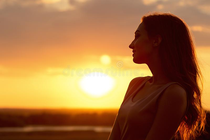 Силуэт красивой девушки на заходе солнца в поле, лобовом профиле молодой женщины наслаждаясь природой стоковая фотография