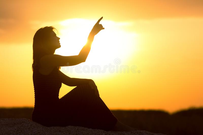 Силуэт красивой девушки сидя на песке и наслаждаясь заходом солнца, диаграммой молодой женщины на пляже показывая вверх с стоковая фотография