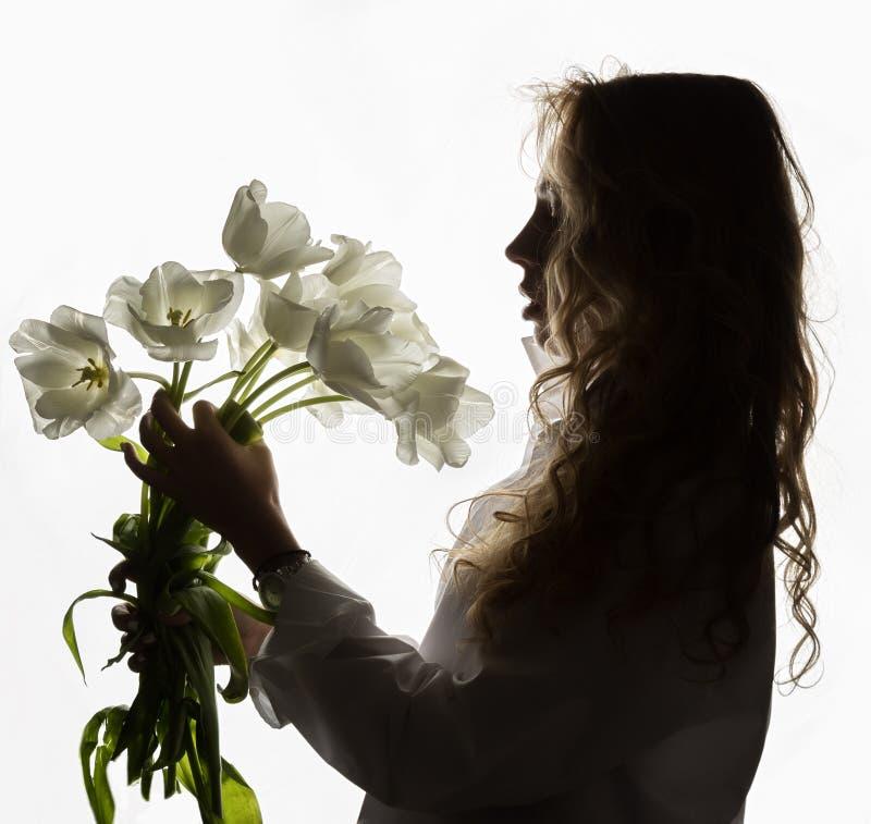Силуэт красивой курчавой девушки с весной цветет тюльпаны на белой предпосылке стоковое изображение rf