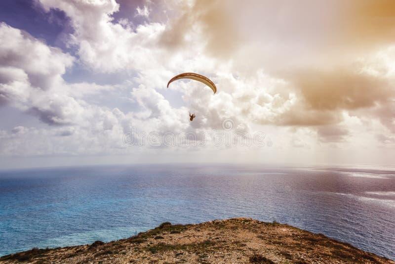 Силуэт летания человека на параплане высоком над морем внутри стоковая фотография