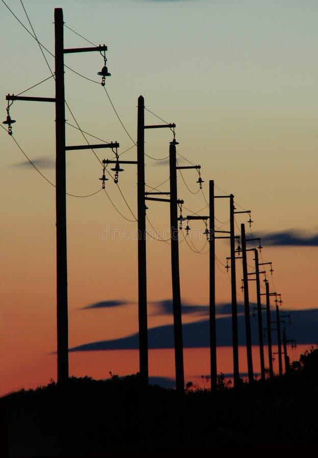 Силуэт линий электропередач во время захода солнца стоковые изображения