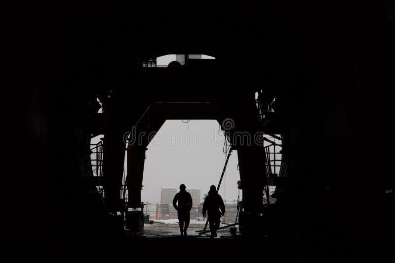 Силуэт 2 людей в высокоскоростном железнодорожном тоннеле под конструкцией стоковые фотографии rf