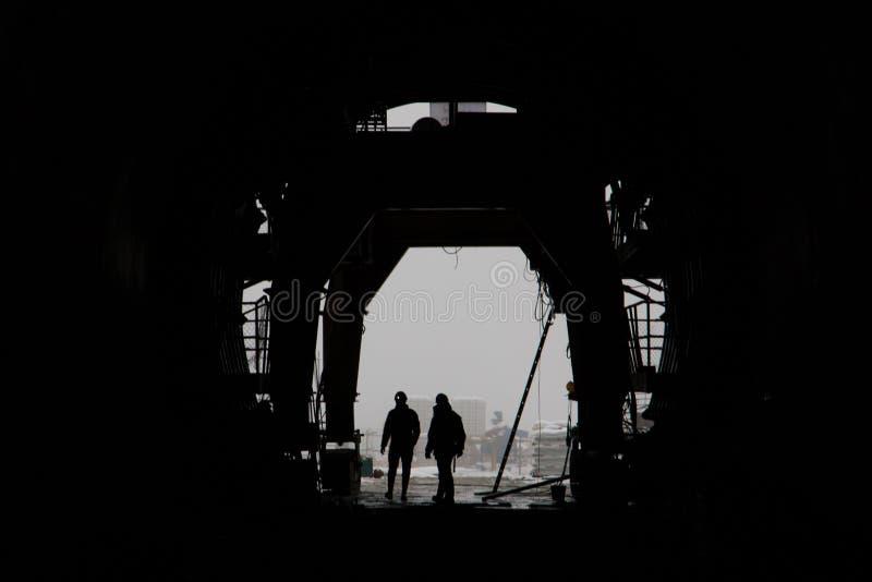 Силуэт 2 людей в высокоскоростном железнодорожном тоннеле под конструкцией стоковая фотография rf